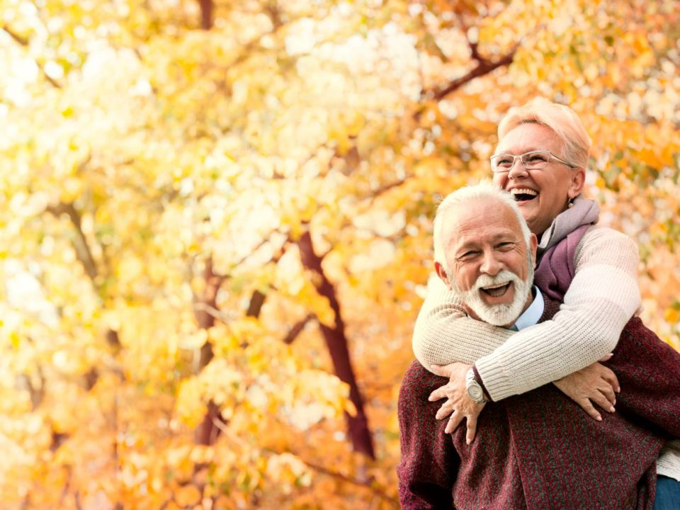 Older couple walking together in the woods considering Medicare options